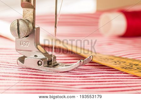 The Sewing Machine's Foot With A Needle Sews Fabric