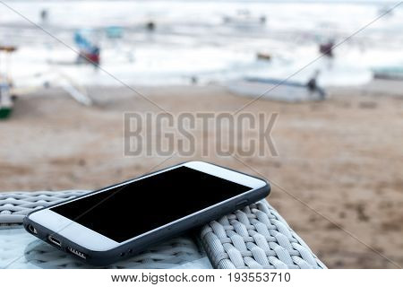 Man hand with smartphone with empty space on a beach background.