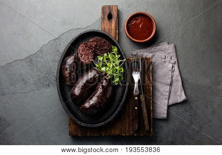 Bloody sausages - chilean preta on black iron plate, top view, grey slate background