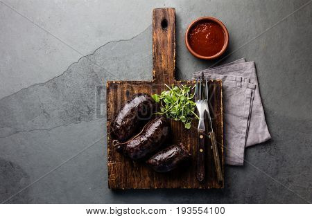 Bloody sausages - prieta on wooden board with chili sauce, slate background
