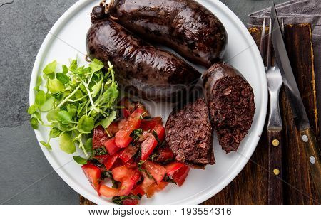 Bloody sausages served on white plate with salad, top view