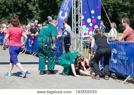 Southampton, Uk - 2 July 2017: Athlete, suffering from heat exhaustion, is help by paramedics at the finish line of Race for Life. This annual race is run by women to raise money for Cancer Research.