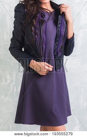 Young slender fashionable brunette woman in a beautiful purple short dress in a black leather jacket. gray background