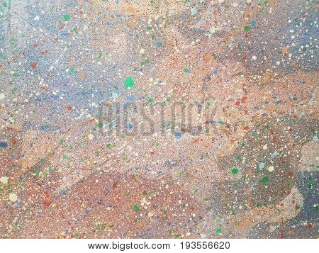 various colored paint speckles on a rough surface