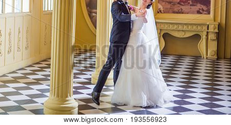 Cropped photo of Side view of wedding couple kissing white standing against wall covered with pink flowers