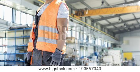 Portrait of smiling young manual worker standing in factory