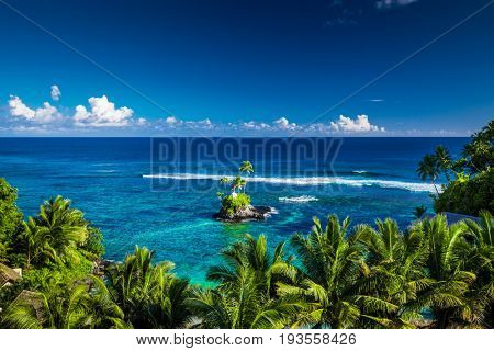 Tropical beach on Samoa Island with palm trees on a small island, Upolu