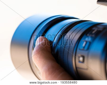 Close up of a camera telephoto lens being hand held by a photographer
