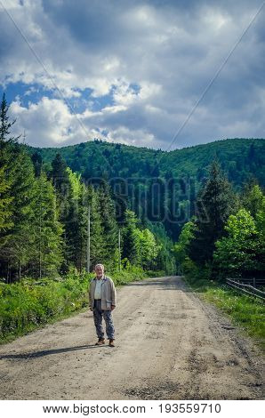 Full length portrait of a handsome senior man in the beautiful place. Looking at the camera. Serious senior man with gray hair and beard on the mountains road. Vertical image.