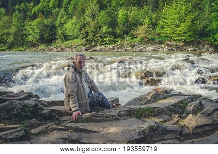 Senior man is sitting and thinking near the waterfall in the beautiful place. Looking at the camera. Serious senior man with gray hair and beard. Horizontal image.