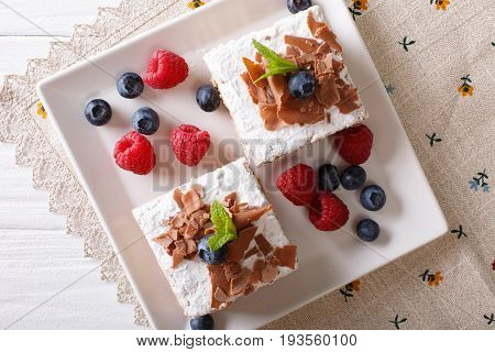 Sliced Chocolate Cake With Raspberries And Blueberries Close-up On A Plate. Horizontal Top View