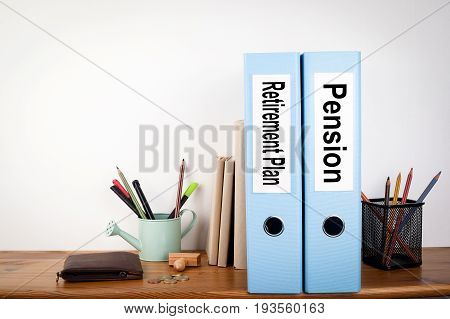Retirement Plan and Pension binders in the office. Stationery on a wooden shelf.