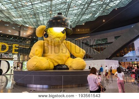 Doha Qatar - May 31 2017: The big yellow lamp teddy bear in the middle of the terminal at the Hamad International Airport Doha Qatar.
