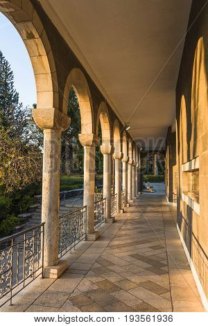 The last rays of the setting sun lit up the colonnade of the Orthodox Church on the steep Bank of the sea of Galilee. Israel.
