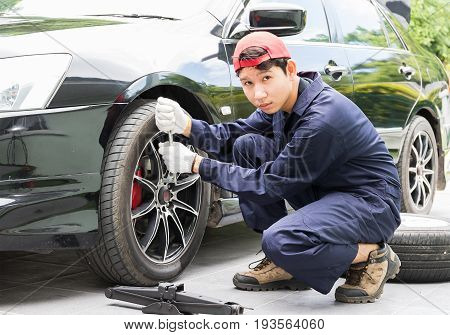 Mechanic Replacing Lug Nuts Changing Tires On Vehicle