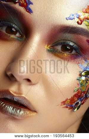 Gorgeous model with colorful creative makeup in studio photo. Vibrance and colors.