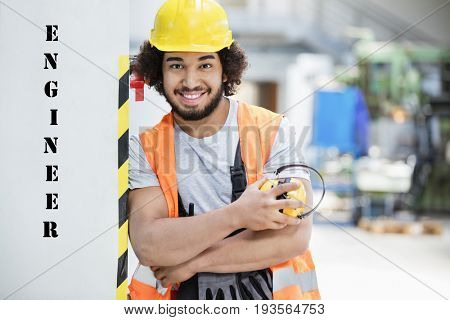 Portrait of confident male worker in protective clothing holding ear protectors at factory with the text saying Engineer next to him on the wall