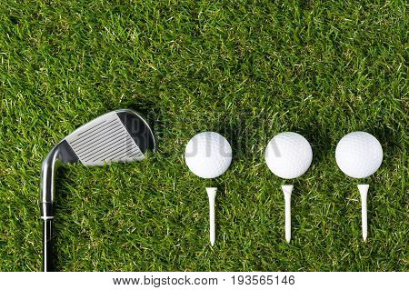 Golf club and three balls lie beautifully on the green grass