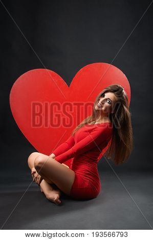 Vertical studio shot of an attractive young woman sitting near big red heart on the floor smiling happily to the camera femininity sensuality seduction affection love emotions valentines day.