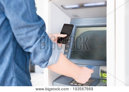 Man hand inserting a credit card in an atm holding smart-phone
