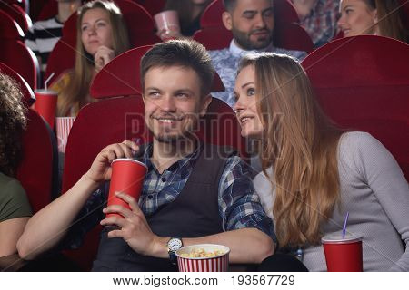 Happy young couple having a date at the cinema enjoying watching a movie together romance relationships romantic dating boyfriend girlfriend entertaining activity weekend.