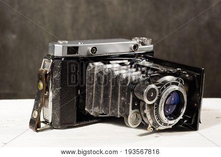 Old Vintage Camera On White Wooden Table Black Background