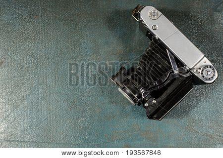 Old Vintage Camera On A Blue Scratched Background.