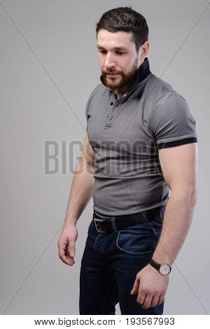 Brutal Muscular Male Dressed In A T-shirt Over Grey Background.