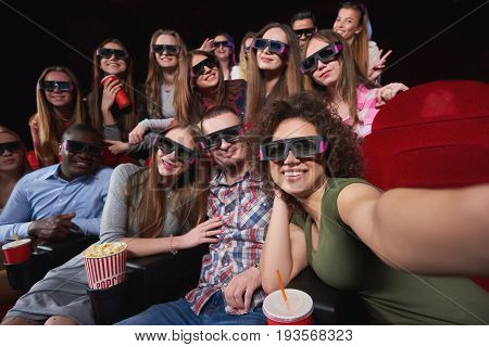 Group of cheerful friends wearing 3D glasses smiling happily taking a selfie relaxing at the cinema together happiness memories people entertainment activity recreation concept.