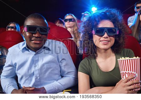 Cheerful African man and his girlfriend wearing 3D glasses holding popcorn smiling to the camera while enjoying a movie together couples dating romance friends friendship leisure entertainment.