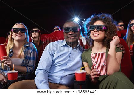 Low angle shot of a happy African man smiling to the camera hugging his beautiful girlfriend during date at the cinema watching 3D movie people leisure entertainment couple romance cuddling.