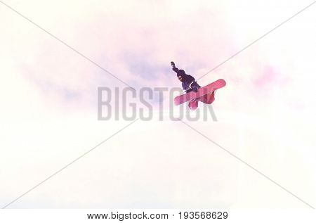 Low angle view of a person on snowboard jumping midair against the sky