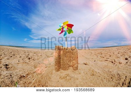 Sand castle with pinwheel on beach