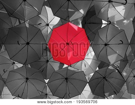 Bright red outstanding umbrella hanging among black umbrellas. Individuality and difference concept.