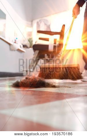 Hairdresser sweeping hair clippings on floor in barber shop