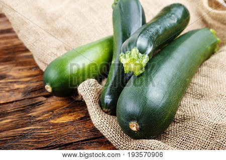Whole zucchini on a wooden background on sacking