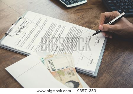 Businessman signing contract with money South Korean won banknotes on the table - loan bribery and corruption concepts