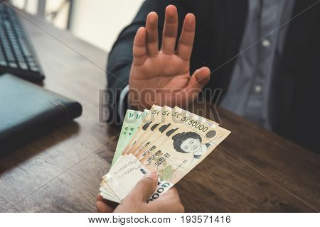 Businessman rejecting money - anti bribery concept