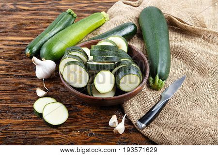 Cut courgettes with garlic there is a knife and burlap next to it