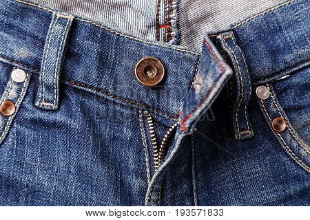 Unbuttoned zipper on old blue jeans. Background and texture