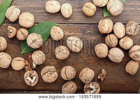 Whole walnuts in the shell are scattered on a wooden background with walnut leaves