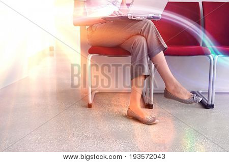 Lowsection of a female executive using laptop on chair in corridor