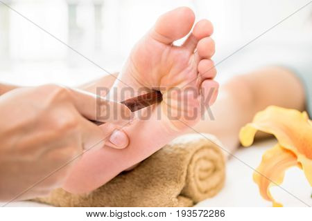 Professional therapist giving traditional thai foot massage with stick to a woman in spa