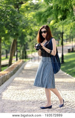 Young woman (photographer tourist) in a blue skirt and black top holds a camera in her hand. Selective focus.