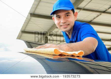 A man polishing car with microfiber cloth car detailing or valeting concept