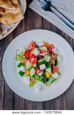 Greek salad in white plate on wooden table background. Vegan vegetarian food content.Top view with copy space
