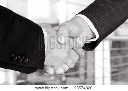 Handshake of businessmen in black and white tone - greeting dealing mergers and acquisition concept