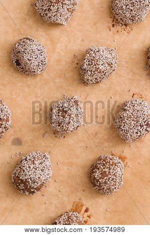 Top view on dark chocolate coconut brownie energy bites. Oatmeal balls / Oats dates energy balls. Vegan sweet delicious nut cocoa balls. Healthy and tasty food concept