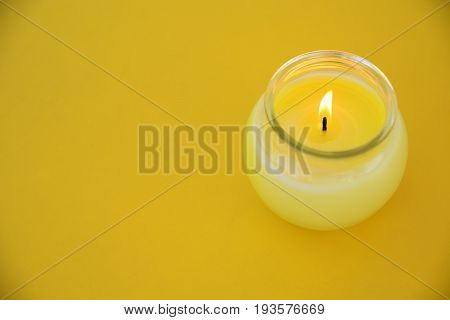 Yellow minimalistic centerpiece with a citronella candle in a glass. Empty copy space for Editor's text.