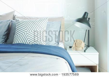 Modern Classic Style Interior Bedroom With Pillows And Black Reading Lamp On Bedside Table
